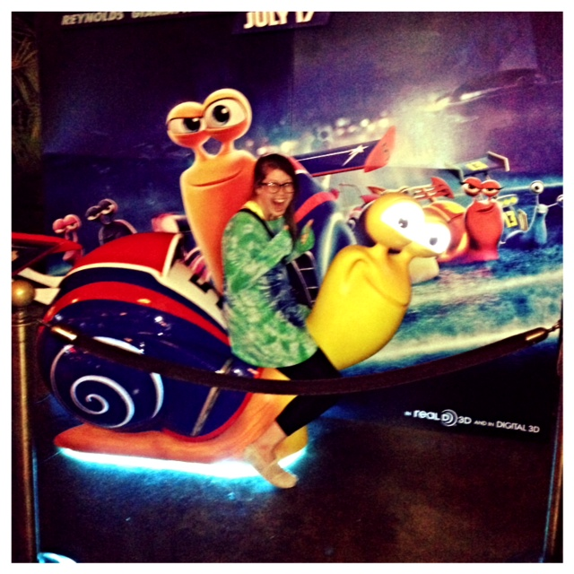 Lauren rides a giant snail at the movie theatre